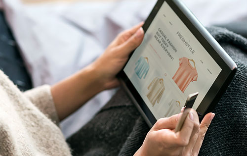 person scrolling through clothing website on tablet