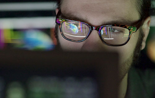 person with glasses behind a computer screen