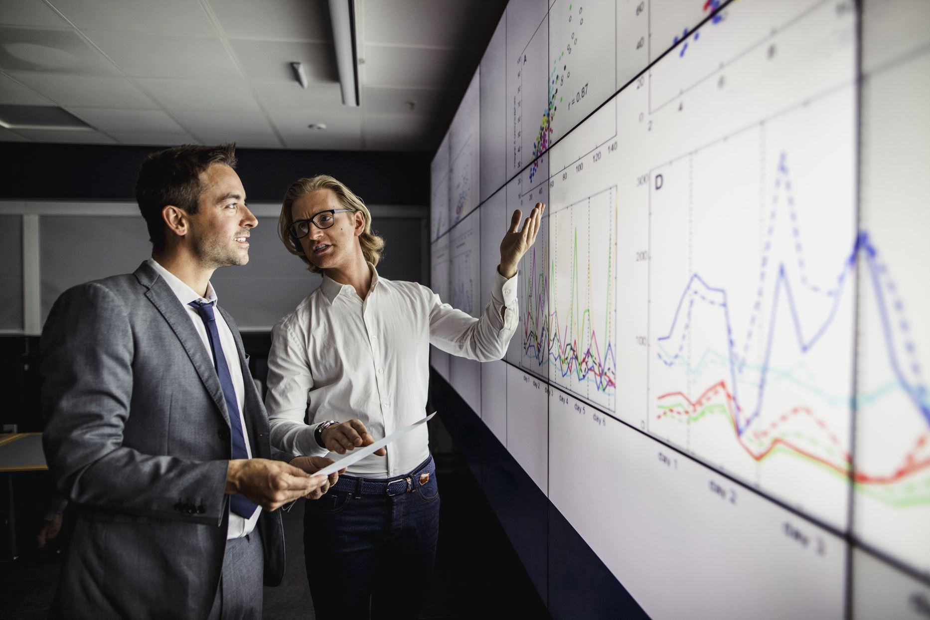 two people looking at graphs on the board and talking