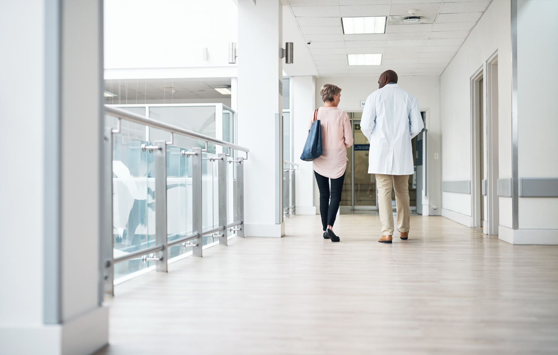 doctor and a patient walking at hospital hall