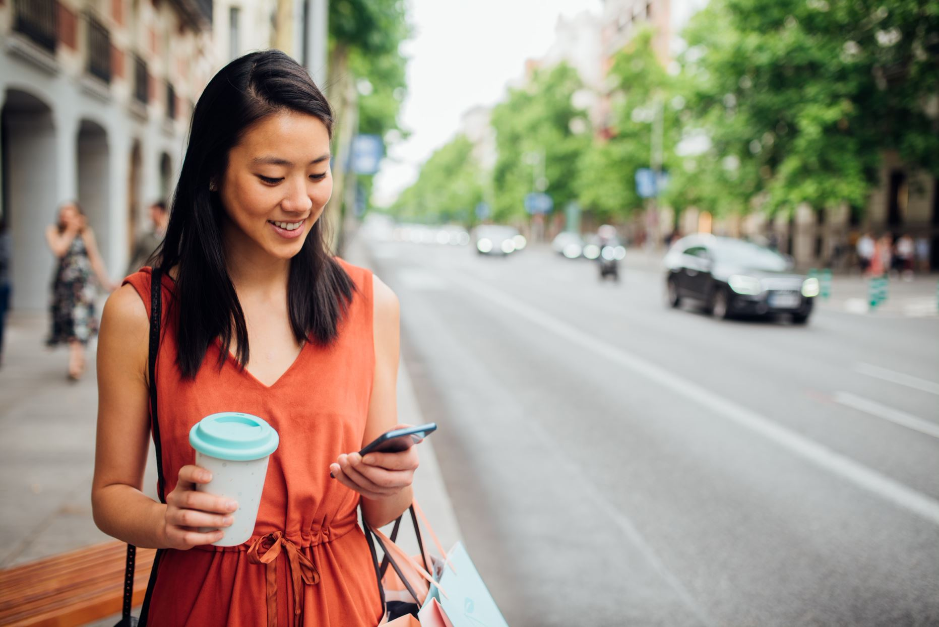 person with a cup of coffee walking on the street and checking her phone