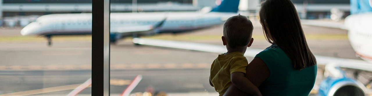 A mother and son watch air planes at the airport
