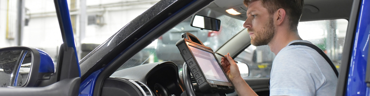 Mechanic working on a tablet in a vehicle