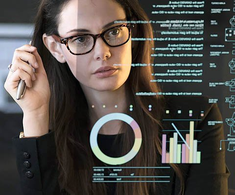 woman with glasses looking at graphs on the screen