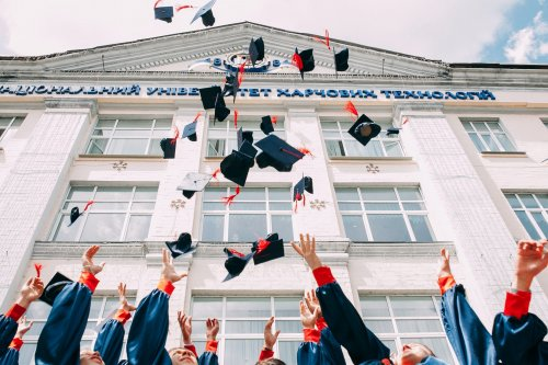graduates throwing their hats