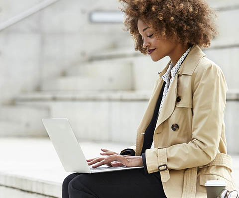 woman in a trench coat with a laptop