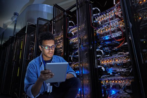 Technician using a tablet next to a server cabinet